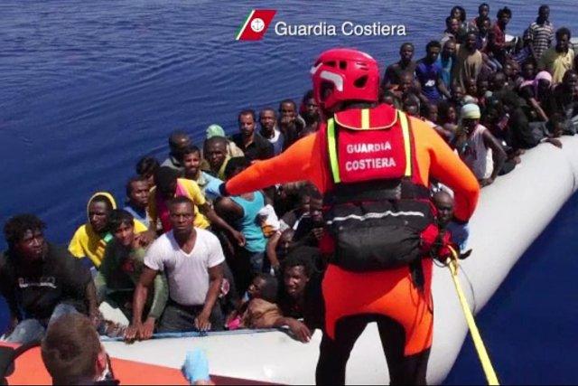 Un garde-côte italien s'adresse à des migrants accostant... (PHOTO archives AFP/GARDE CÔTIÈRE ITALIENNE)