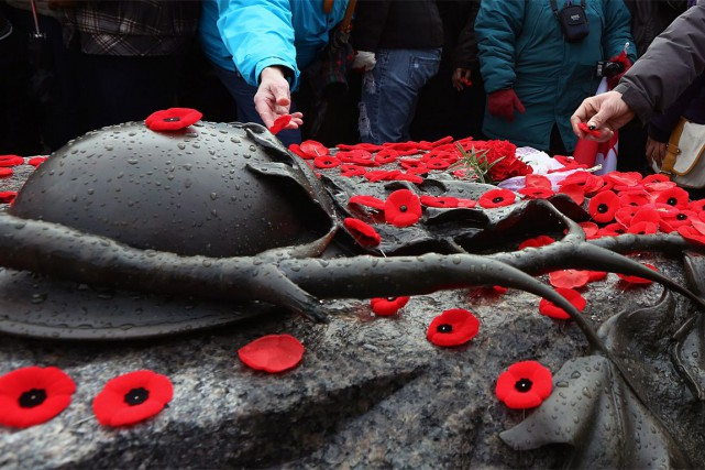Des gens déposent leurs coquelicots sur la tombe... (ARCHIVES, La Presse Canadienne)