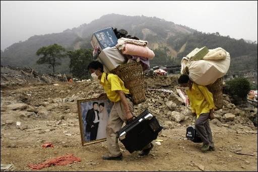 Des victimes du séisme en Chine transportent leurs... (Photo archives AP)