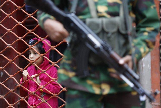 Une jeune fille observait hier les électeurs bangladais... (Photo Andrew Biraj , Reuters)