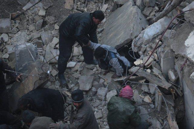 Un homme fouille dans les décombres après un... (Photo BASSAM KHABIEH, Reuters)