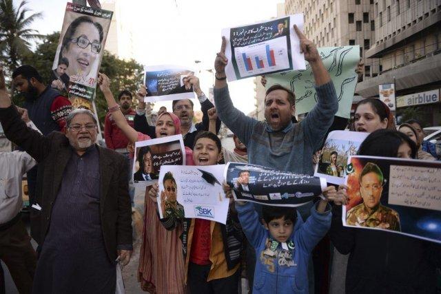 Des partisans dePervez Musharraf brandissent des affiches avec... (PHOTO ASIF HASSAN, AFP)
