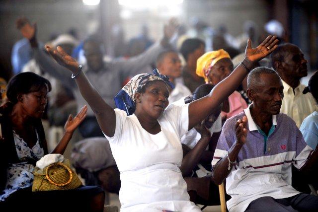 Des Haïtiens assistent à une messe commémorative dans... (PHOTO HECTOR RETAMAL, AFP)