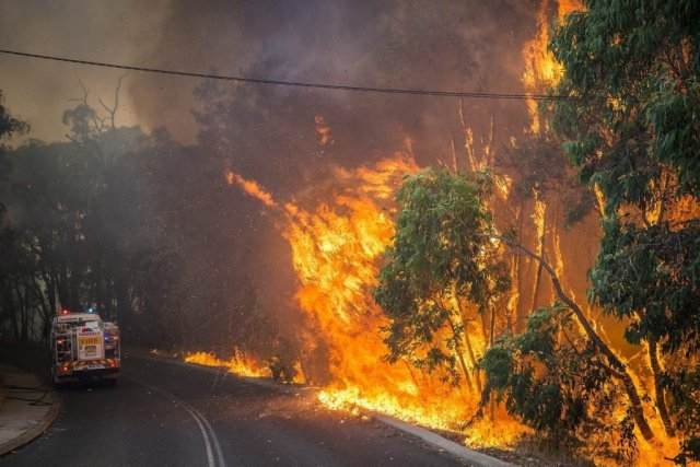 Le feu fait rage le long d'une route... (PHOTO ASSOCIATED PRESS)
