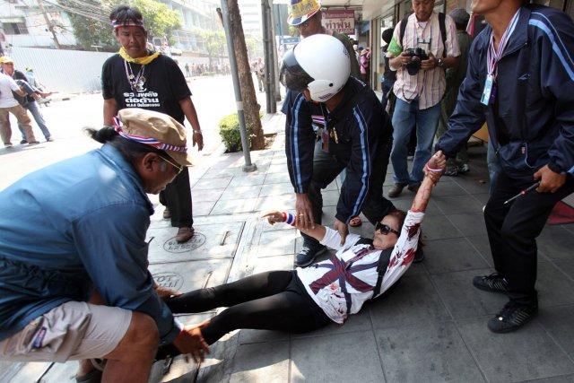 Une femme blessée est évacuée par d'autres manifestants.... (PHOTO AFP)