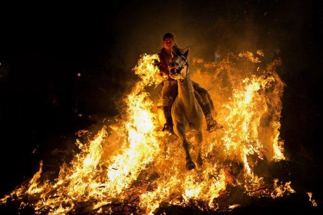 Un homme et son cheval traversent un bûcher.... (PHOTO EMILIO MORENATTI, AP)