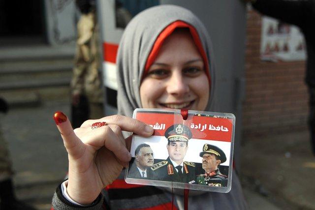 Une Égyptienne brandit les portraits des anciens présidents... (PHOTO AFP)