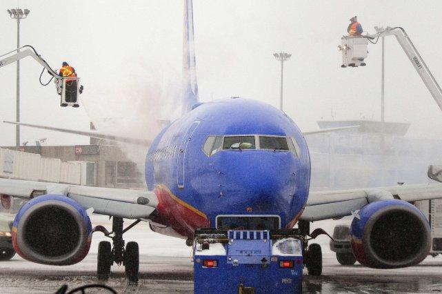 Des employés déglacent un avion.... (Photo DOMINICK REUTER, Reuters)