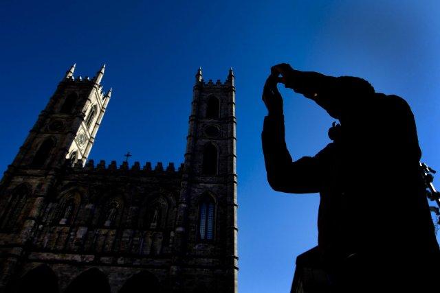 Un touriste à côté de la Basilique Notre-Dame... (Photo Brent Lewin, Bloomberg)