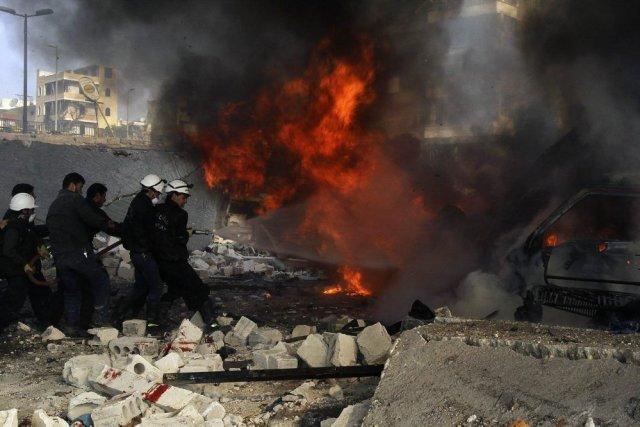 Des pompiers éteignent des véhicules en feu, dans... (Photo AMMAR ABDULLAH, Reuters)