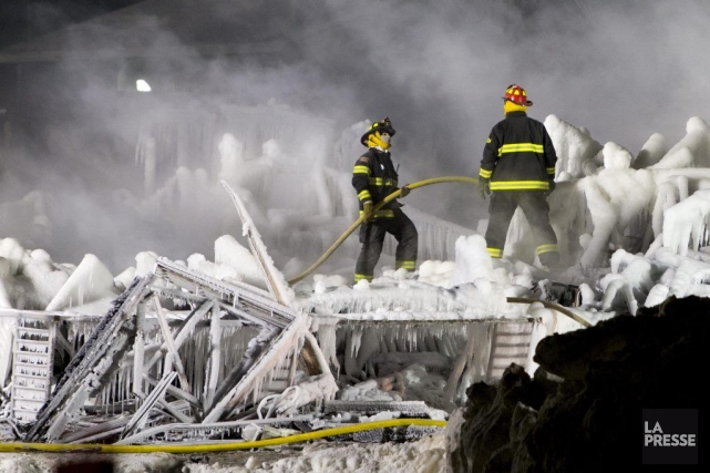 Les pompiers éteignent le brasier.... (Photo Alain Roberge, La Presse)