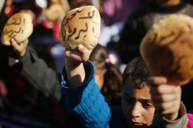 Des enfants palestiniens brandissent des pains en guise... (PHOTO MOHAMMED SALEM, REUTERS)
