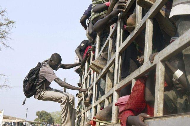 Des réfugiés montent à bord d'un camion au... (PHOTO ISAAC KASAMANI, AFP)