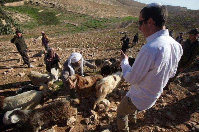 Un colon israélien réprimande un berger palestinien, au... (Photo: AFP)