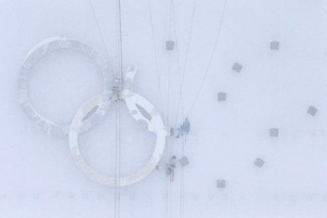 Des travailleurs construisent les anneaux olympiques sur le... (Photo: Reuters)