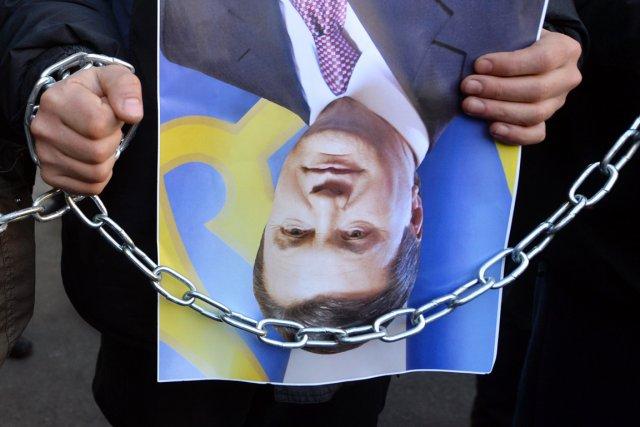 Un manifestant tient une photo du président Ianoukovitch... (PHOTO SERGEI SUPINSKY, ARCHIVES AFP)