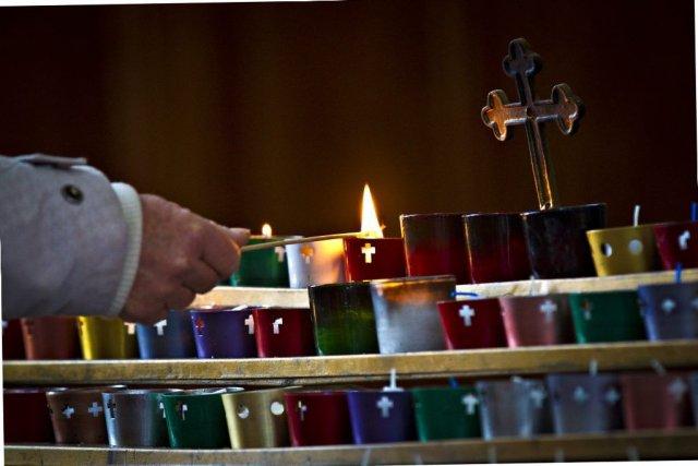 Une jeune femme allume un lampion dans l'église... (PHOTO OLIVIER JEAN, LA PRESSE)