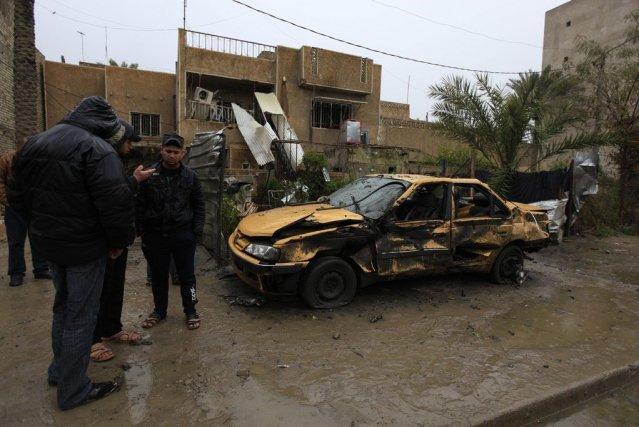 Des hommes regardent une voiture qui a explosé,... (Photo Reuters)
