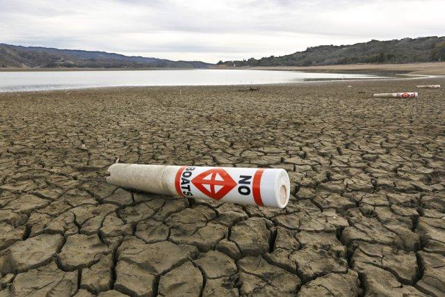 Une bouée d'avertissement repose sur une terre craquée... (PHOTO RICH PEDRONCELLI, AP)