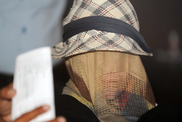 Le visage couvert d'un foulard et d'un chapeau,... (Photo: AFP)