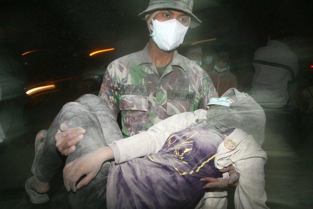 Un soldat porte une femme qui s'est évanouie... (PHOTO AMAN ROCHMAN, AFP)