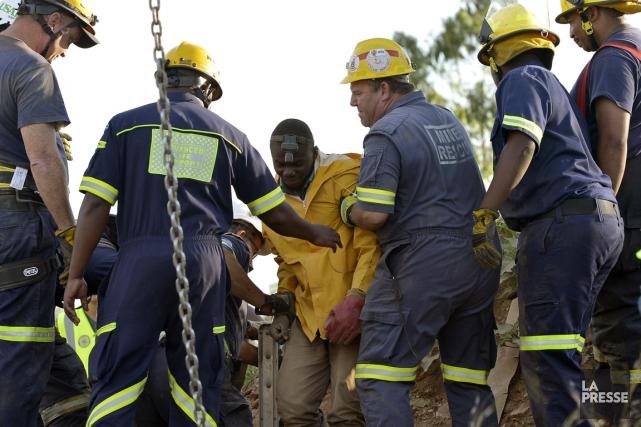 Les hommes sont sortis à l'aide d'une échelle... (PHOTO ALEXANDER JOE, AFP)