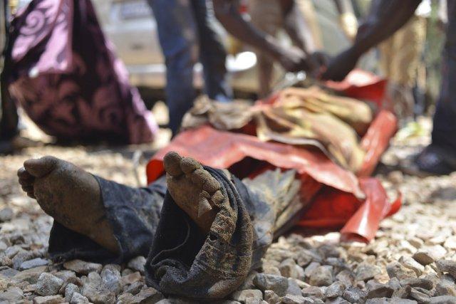 Des parents et des proches entourent le corps... (Photo Mujahid Safodien, Reuters)