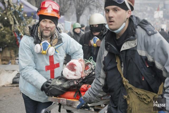 Des secouristes évacuent un manifestant blessé, à la... (PHOTO EFREM LUKATSKY, AP)