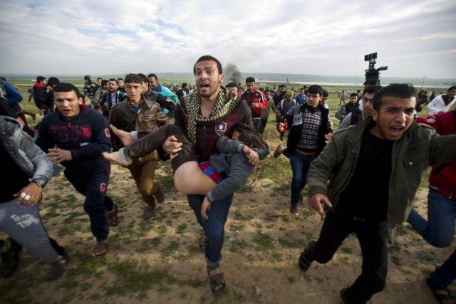 Un homme porte le corps blessé d'un jeune... (Photo Mahmud Hams, AFP)