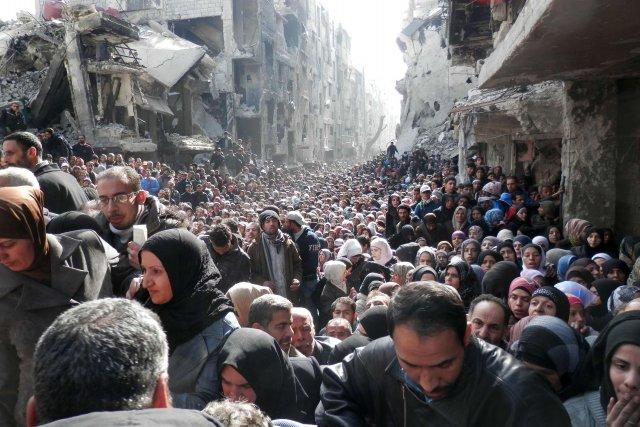 Des réfugiés regroupés lors d'une distribution de produits... (Photo AFP)