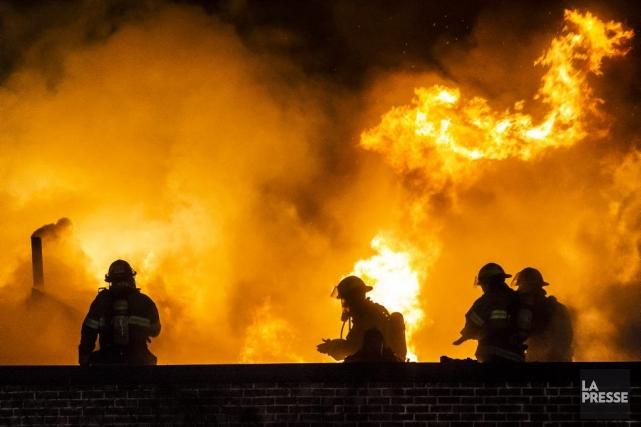 Les pompiers tentent de maîtriser un immense feu... (PHOTO OLIVIER PONTBRIAND, LA PRESSE)