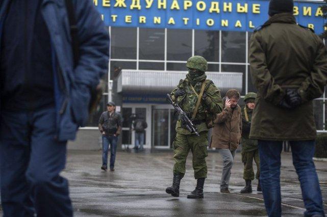 Des hommes armés en uniforme patrouillaient vendredi devant... (PHOTO ANDREW LUBIMOV, AP)