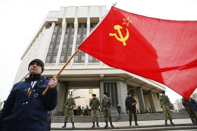Un homme brandit un drapeau soviétique alors qu'il... (PHOTO DAVID MDZINARISHVILI, REUTERS)