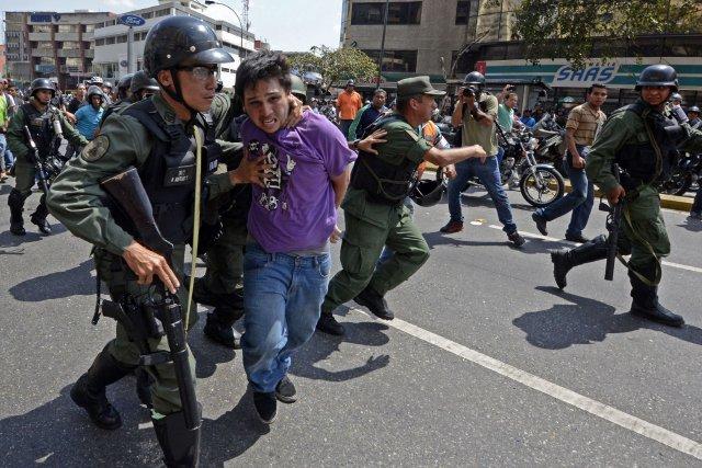 Un manifestant se fait arrêter par des membres... (PHOTO JUAN BARRETO, AFP)