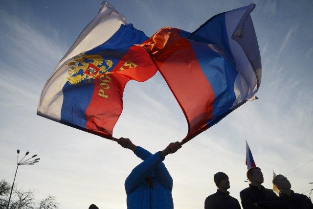 Un manifestant brandit deux drapeaux de la Russie... (PHOTO MARK LEVIN, REUTERS)