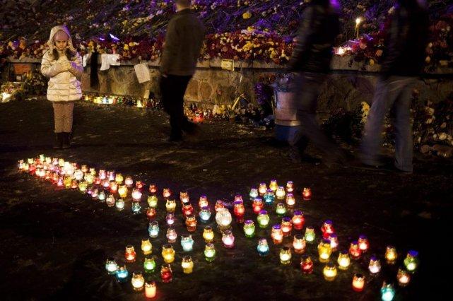 Une jeune fille regarde des bougies placées pour... (PHOTO DAVID AZIA, AP)