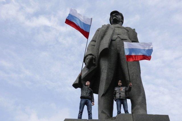 Deux manifestants ont grimpé sur lastatue de Lénine... (PHOTO KONSTANTIN CHERNICHKIN, REUTERS)