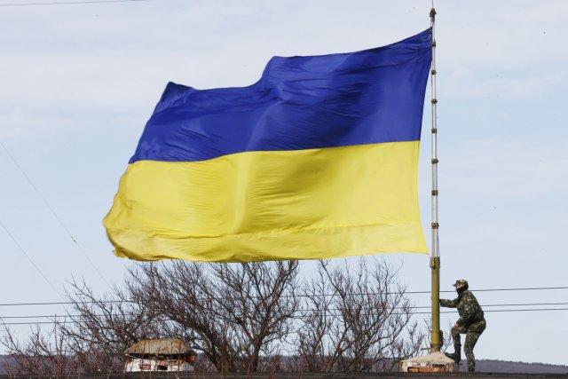 Un soldat ukrainien monte sur le toit d'un... (PHOTO THOMAS PETER, REUTERS)