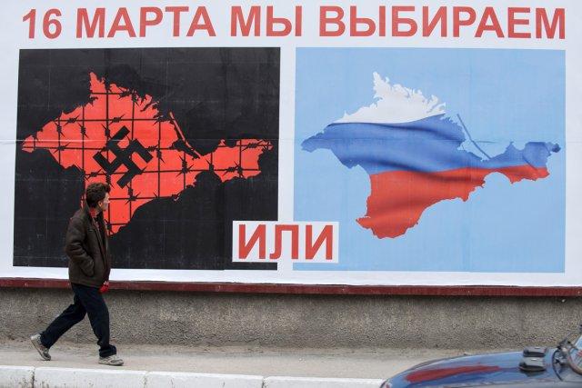 Un homme passe devant une affiche électorale annonçant... (PHOTO ANDREW LUBIMOV, AP)