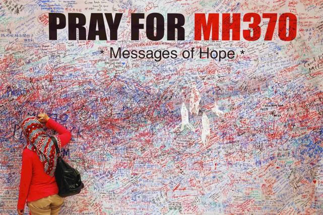 À Kuala Lumpur, une femme écrit un message... (PHOTO DAMIR SAGOLJ, REUTERS)