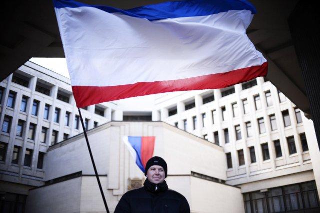 Un homme tient un drapeau russe devant le... (PHOTO DIMITAR DILKOFF, AFP)
