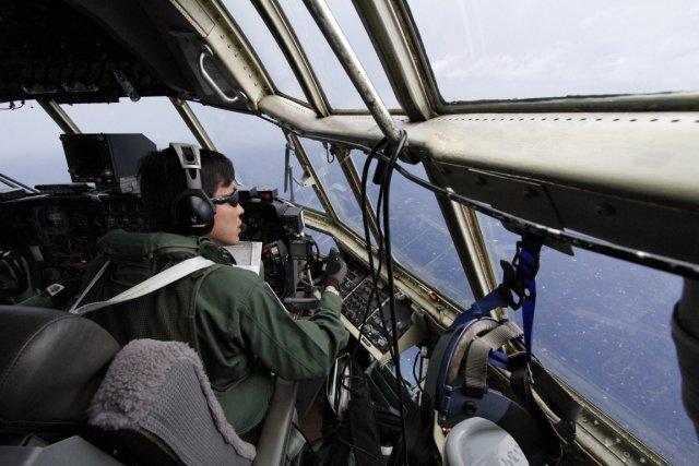 Un co-pilote des forces aériennes japonaises scrute l'océan... (Photo Koji Ueda, AP)