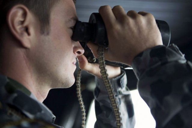 Un officier participe aux recherches à bord du... (PHOTO REUTERS)
