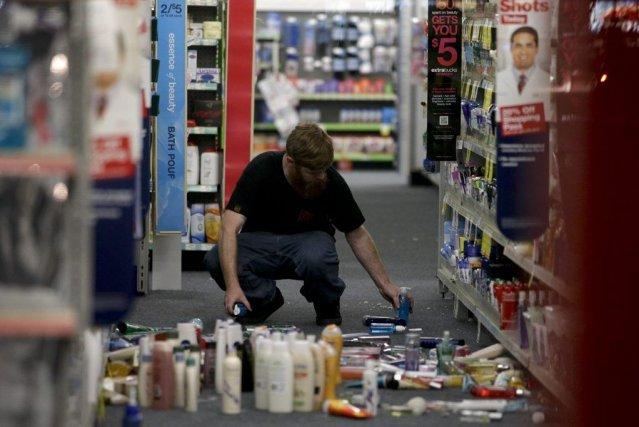 Un homme ramasse des articles tombés lors du... (PHOTO JAE C. HONG, AP)