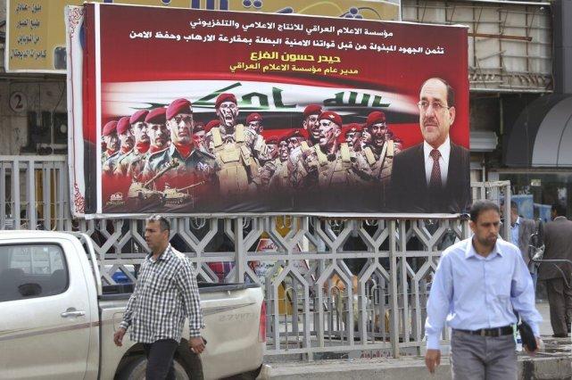 Des Irakiens passent devant une affiche électorale du... (Photo AHMAD AL-RUBAYE, AFP)
