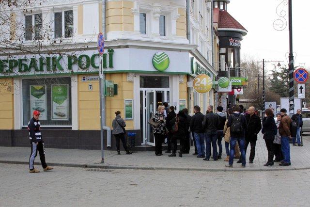 Des Ukrainiens font la file pour retirer de... (Photo Reuters)