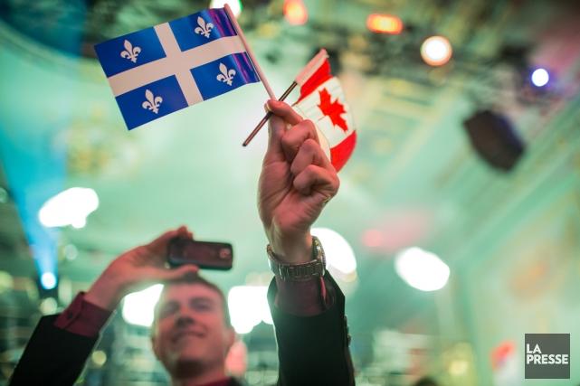 Un partisan libéal photographie des drapeaux du Québec... (Photo Olivier PontBriand, La Presse)