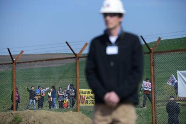 Des manifestants anti-gaz de schiste derrière une clôture... (Photo AFP)