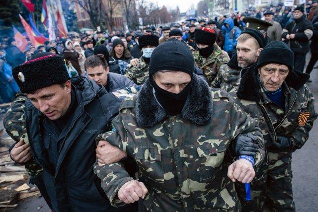 Des activistes pro-russes escortent un homme accusé d'être... (PHOTO DIMITAR DILKOFF, AFP)