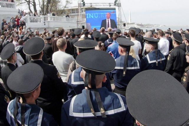 Des résidants et des marins russes regardent le... (PHOTO VASILY BATANOV, AFP)